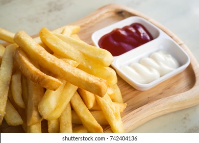Fresh homemade french fries on wooden plate. served with tomato sauce. Favorite snack of fast food. High calories and unhealthy.