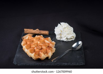 Fresh homemade gofre with chocolate syrup above in top view isolated on stone slate background - Image with chocolate syrup, whipped cream and cinnamon top view isolated on slate stone background