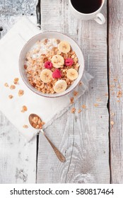 Fresh homemade granola with berries, bananas, nuts, seeds and honey bathed in milk with chicory drink - healthy breakfast on white wooden background. top view. copy space