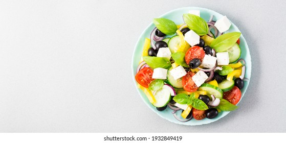 Fresh homemade greek salad with basil leaves on a plate on the table. Domestic life. Top view. Copy space. Web banner