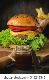 Fresh homemade hamburger with black sesame seeds on wooden cutting board with french fries potatoes, served with ketchup sauce in glass jar over wooden table with dark background. Dark rustic style.
