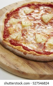 Fresh Homemade Hawaiian Pizza served on wooden plate ( with Mozzarella, Fresh Pineapple and Ham ), white background, close up