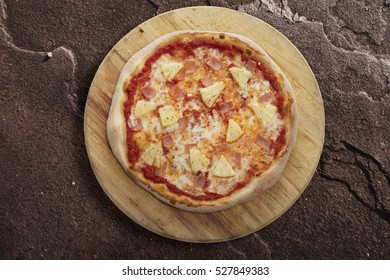 Fresh Homemade Hawaiian Pizza served on wooden plate ( with Mozzarella, Fresh Pineapple and Ham ), rock background, close up