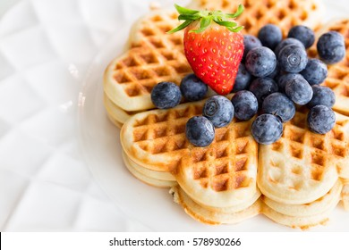 Fresh homemade heart shape waffles with blueberries and strawberry on white plate