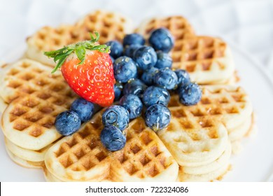 Fresh homemade heart shape waffles with blueberries and strawberry, close up