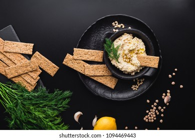 Fresh homemade hummus with vegan crackers and ingredients scattered around, top view