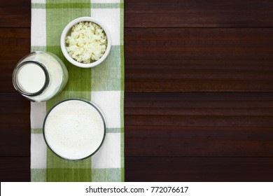 Fresh homemade kefir drink in glass with kefir grains and milk on the side, photographed overhead with natural light (Selective Focus, Focus on the kefir drink)