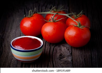 Fresh homemade ketchup and toamtoes composition. Vegetables and sauce photography taken on rustic old table.