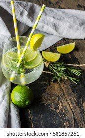 Fresh homemade lemonade with lime, lemon, rosemary and ice on rustic wooden table with copyspace