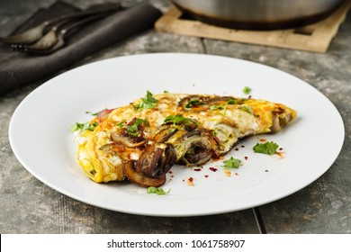 Fresh homemade omelette with mushrooms, feta cheese and herbs.