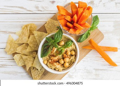 Fresh homemade organic hummus with pita cheaps and basil, carrot sticks and ingredients on wooden table. Healthy food concept. Selective focus