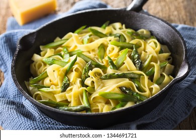 Fresh homemade pasta dish of fettuccine or tagliatelle, green asparagus, garlic and lemon juice in cast iron skillet (Selective Focus, Focus one third into the frying pan)