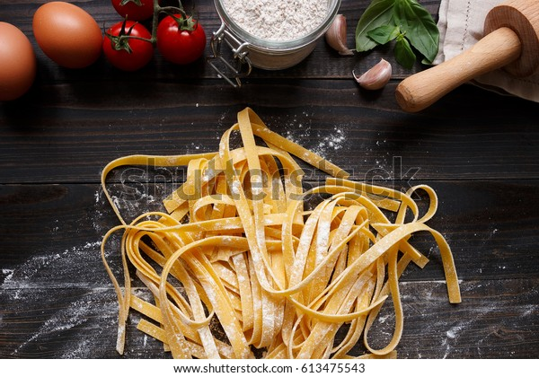 Fresh homemade pasta with pasta ingredients on the dark wooden table top view.