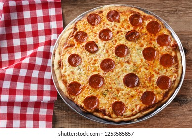 Fresh Homemade Pepperoni Three Cheese Pizza on a red checkered table cloth on a wood table with copy space, horizontal format.