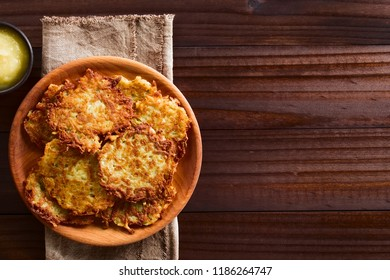 Fresh homemade potato fritters or pancakes with apple sauce on the side, a traditional German snack or dish called Kartoffelpuffer or Reibekuchen, photographed overhead with copy space on the side