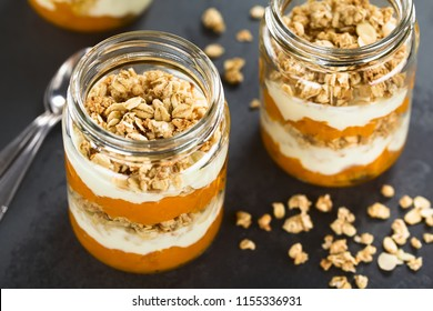 Fresh homemade pumpkin puree, yogurt and granola parfait breakfast, snack or dessert, served in glasses, photographed on slate (Selective Focus, Focus in the middle of the granola on first parfait)