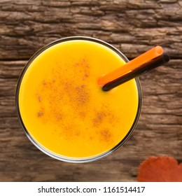 Fresh homemade pumpkin smoothie with cinnamon in glass with drinking straws, photographed overhead on wood (Selective Focus, Focus on the drink)