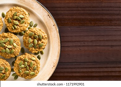 Fresh homemade pumpkin walnut oatmeal muffins with pepita pumpkin seeds on top on plate, photographed overhead with copy space (Selective Focus, Focus on the top of the muffins)