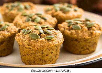 Fresh homemade pumpkin walnut oatmeal muffins with pepita pumpkin seeds on top (Selective Focus, Focus on the first two seeds on the first muffin)