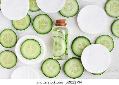 Fresh homemade refreshing facial toner in bottle, green cucumber slices, cotton-pads, top view ingredients