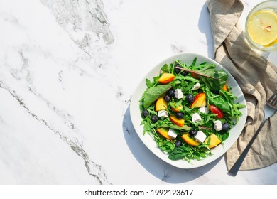 Fresh homemade salad with nectarines, blueberries, arugula, spinach and feta cheese on white marble background with hard shadows. Healthy vegetarian food. Top view. Space for text.