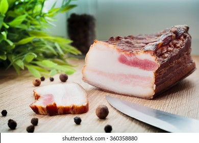 Fresh homemade smoked bacon on a wooden plate