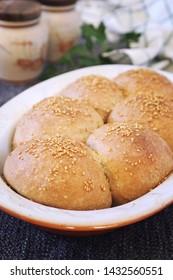 Fresh homemade sourdough bread buns with sesame in ceramic bakeware
