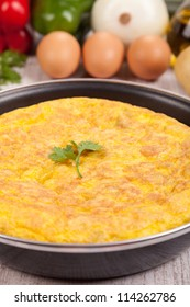 Fresh homemade Spanish tortilla (omelette) in the frying pan, and some ingredients