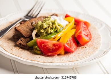 Fresh homemade steak fajitas on a white background top view
