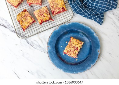 Fresh Homemade Strawberry Bar Cookies Cooling on a Wire Rack on a White Countertop; One Isolated in Front on a Rustic Blue Plate; Blue Kitchen Towel