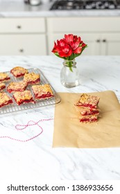 Fresh Homemade Strawberry Bar Cookies Cooling on a Wire Rack on a White Countertop; Some Stacked with Parchment Paper Between