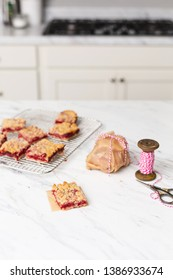Fresh Homemade Strawberry Bar Cookies Cooling on a Wire Rack on a White Countertop; One Isolated in Front on Piece of Parchment Paper; Some Wrapped in Parchment Paper Wrapped in Red and White Twine