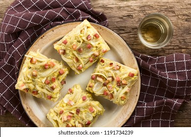 Fresh homemade traditional German Zwiebelkuchen onion cake, savory baked pastry or pie made of yeast dough topped with onion, bacon, eggs, cream, glass of white wine on the side, photographed overhead