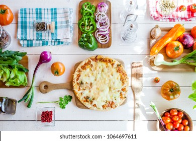 fresh homemade traditional italian cheese pizza on wooden cooking table with ingredients. wallpaper for pizzeria