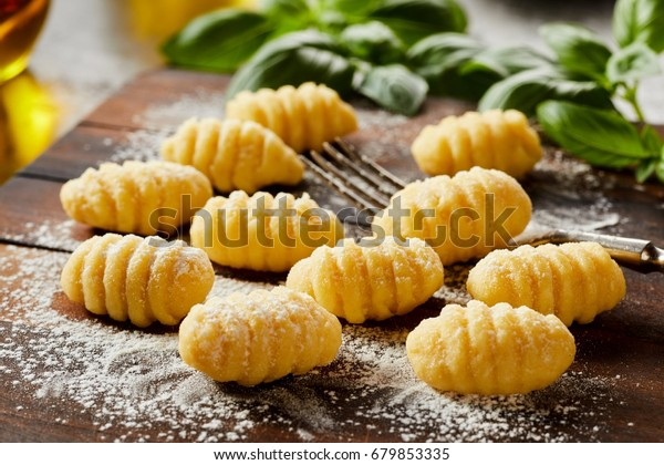 Fresh homemade uncooked gnocchi Italian dumplings on a floured wooden board in a kitchen with fresh basil behind in a close up view