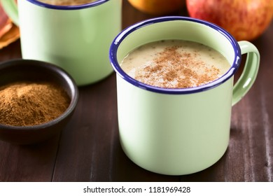 Fresh homemade vegan apple, oatmeal and chia seed smoothie with cinnamon on top, served in enamel cups (Selective Focus, Focus one third into the smoothie)