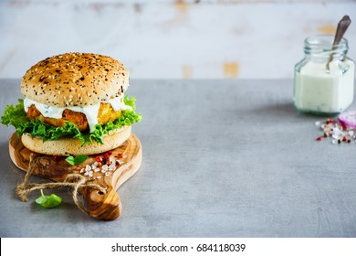 Fresh homemade vegan carrot and oats burger, wholegrain buns on wooden board over stone background, selective focus, copy space.
