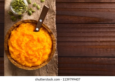 Fresh homemade vegan pumpkin puree or mash in wooden bowl, pumpkin seeds on the side, photographed overhead with copy space on the side (Selective Focus, Focus on the puree)