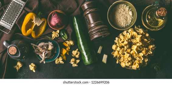 Fresh homemade vegetarian tortellini in bowl on dark rustic table background with vegetables ingredients and vintage  kitchen utensils, top view. Home cuisine. Tortellini cooking