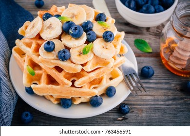 Fresh homemade waffles with blueberries and banana for breakfast on wooden background.