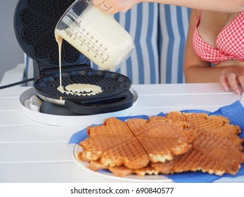 Fresh homemade waffles by woman in bikini, on a white wooden table