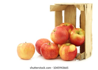 "fresh ""honey crunch"" apples in a wooden crate on a white background"