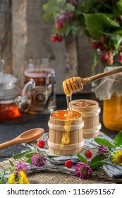Fresh honey drips from a spoon into a wooden bowl. Still life with honey