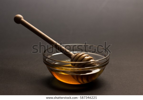 fresh honey in a glass bowl with wooden spoon
