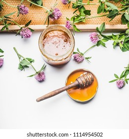 Fresh honey in glass jar with honey spoon, honey comb and wild flowers on white background, top view. Healthy eating and lifestyle