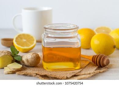 Fresh honey, lemon and ginger on a wooden background