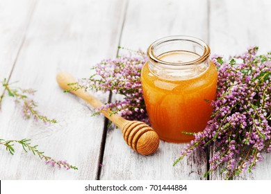 Fresh honey in pot or jar and flowers heather on wooden vintage table. Copy space for text.