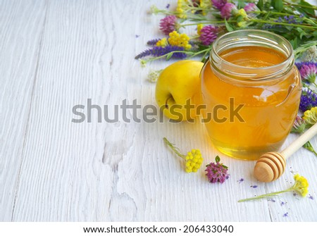 Fresh honey and wild flowers on a white wooden table.