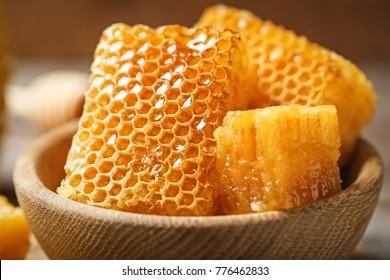 Fresh honeycombs in wooden bowl, closeup