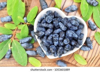 Fresh honeysuckle berries on berries and leaves background